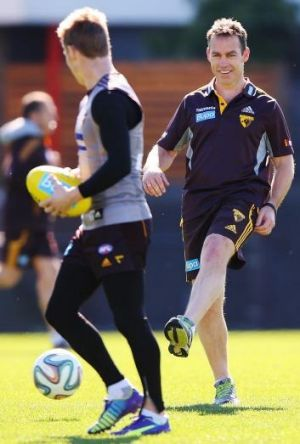 Kicking on: Alastair Clarkson kicks a soccer ball to Sam Mitchell during Hawthorn training on Friday.