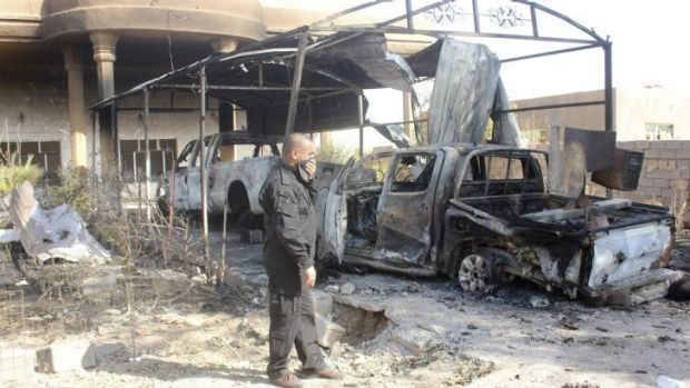 Sectarian violence ... A volunteer with the Iraqi security forces stands next to the wreckage of a vehicle belonging to ...