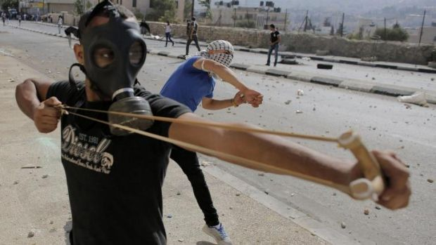 A Palestinian protester uses a slingshot to hurl stones at Israeli troops in Bethlehem.