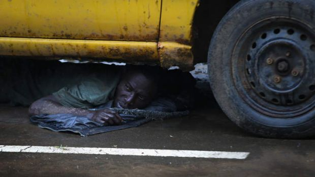 A Liberian man is put under detention and made to lie under a car after showing Ebola symptoms.