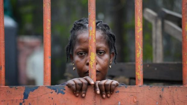 A West Point slum resident looks from behind closed gates on the second day of the government's Ebola quarantine on ...