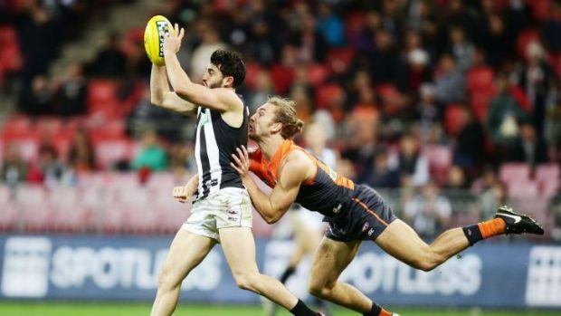 Contest: Collingwood's Alex Fasalo is challenged by Giant Matthew Buntine at Spotless Stadium on Saturday.