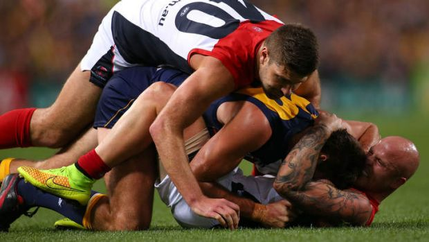Up close and personal: Demons Nathan Jones and Mark Jamar wrestle with Eagle Scott Lycett at Patersons Stadium.