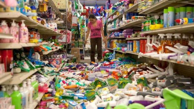 Nina Quidit cleans up the Dollar Plus and Party Supplies Store in American Canyon, California after Sunday's earthquake.