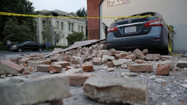Bricks and fallen rubble cover a car following Sunday's earthquake in California.