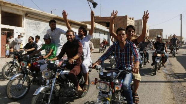 Residents celebrate after the fall of Tabqa airbase.