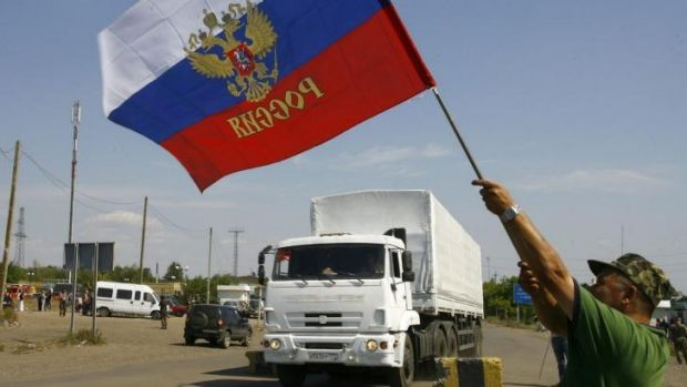 A resident holds a Russian flag as a truck from the previous aid convoy crosses the Ukrainian border. Moscow has vowed ...