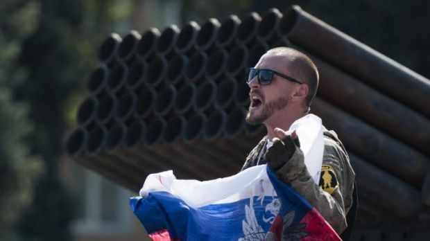 A pro-Russian separatist holds a Russian flag near damaged heavy hardware from the Ukrainian army in Donetsk.
