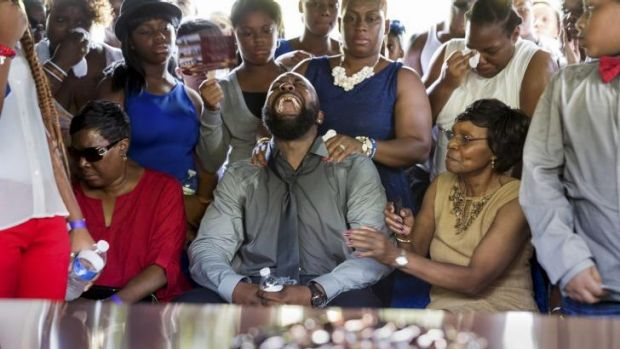 Mourning: Michael Brown snr cries as the coffin of his son is lowered into the ground.