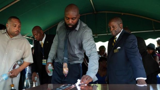 Michael Brown snr wipes the top of the vault containing the casket of his son.