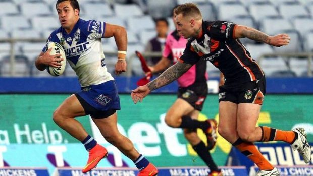 Running on empty: Corey Thompson makes a break against the Tigers in a very sparsely populated ANZ Stadium.