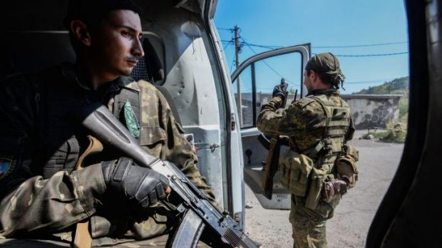 Pro-Russian rebels stand guard at a vehicle used for transportation of mobile military groups in the town of Donetsk, ...