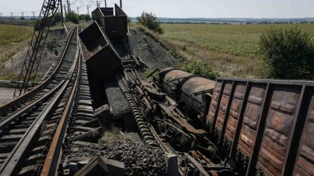 Train wagons on a destroyed railway bridge which collapsed during the fighting between the Ukrainian army and ...