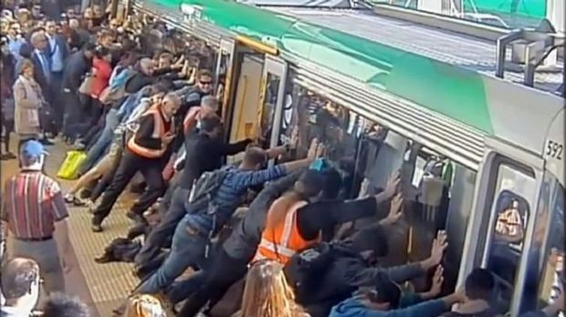 Strength in unity: Perth commuters push against a train to free a passenger's trapped leg.