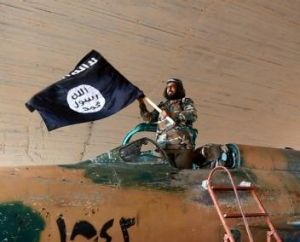 An Islamic State fighter waves its flag at the Tabqa air base, Raqqa.