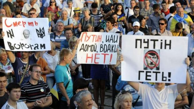 """People hold placards (LtoR) reading """"Putin get out!"""", """"Putin go home, there is no vodka!"""" and """"Death for enemies!"""", ..."""