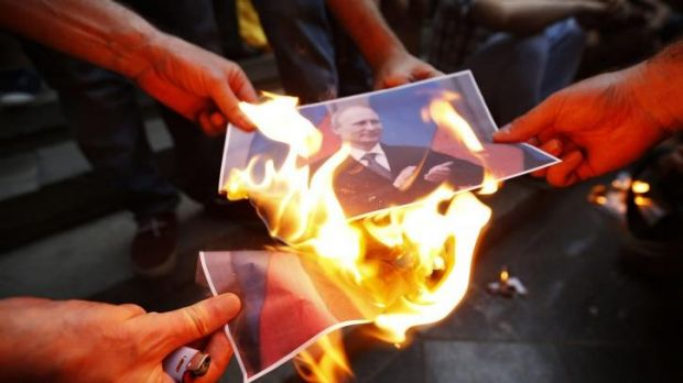 Protesters burn portraits of Russian President Vladimir Putin during a rally in support of Ukraine in Tbilis.