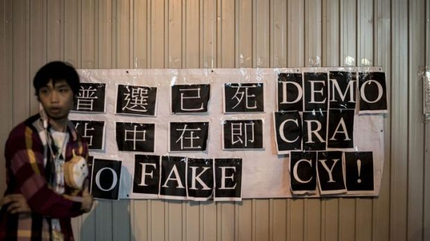 "A protester stands next to a banner that reads ""No Fake Democracy!"" outside government offices in Hong Kong on Friday."