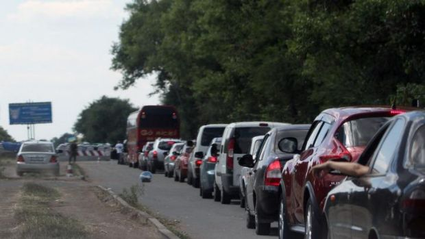 Cars queue at a checkpoint as people flee the southern Ukrainian city of Mariupol amid fears of an attack by pro-Russian ...
