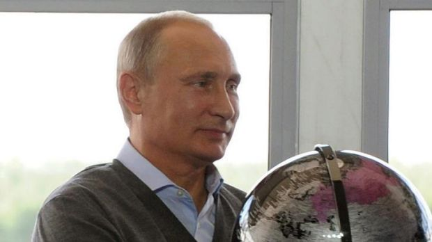 Russian President Vladimir Putin holds a globe presented him as a gift during his meeting with participants in the youth ...