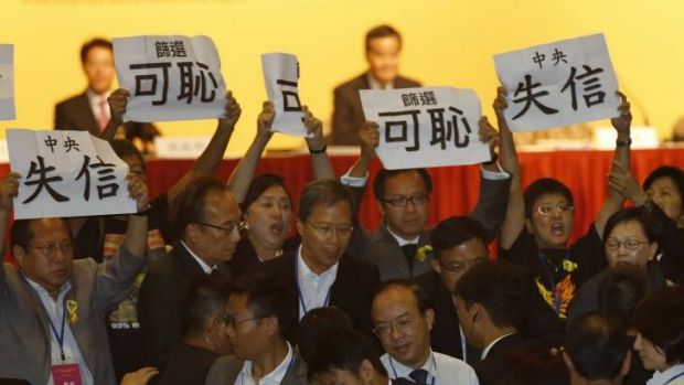 Pro-democracy legislators display placards in protest against the speech of Communist Party official Li Fei on Monday.