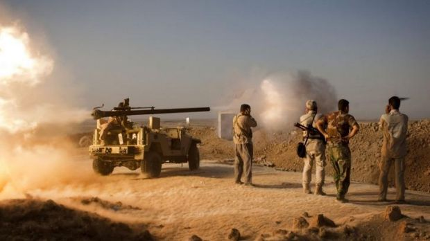 Kurdish fighters fire towards Islamic State positions during clashes south of Kirkuk, Iraq.