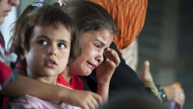Crimes against humanity: A child cries in a military helicopter after being evacuated by Iraqi forces from Amerli, north ...