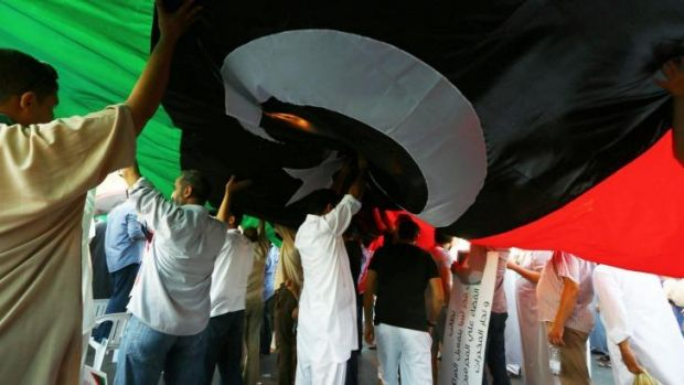 """Libyans deploy a giant national flag during a rally in support of """"Fajr Libya"""" (Libya Dawn)."""