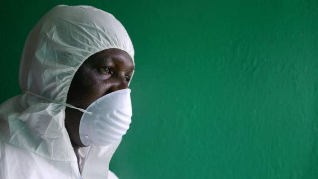 A health worker, wearing a protective suit, conducts an Ebola prevention drill at the port in Monrovia.