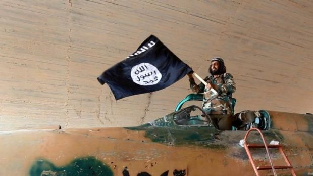 An Islamic State fighter waves the militant group's flag at the Tabqa airbase in Raqqa.