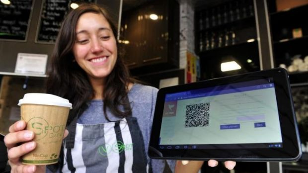 V Spot Cafe assistant manager Monica Furastec Danilevicz shows how the cafe accepts bitcoin payment.