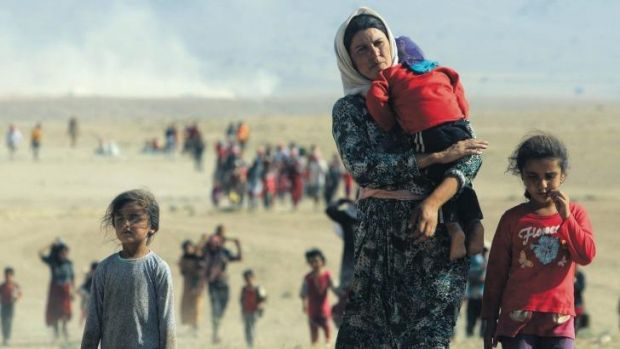 Sold as wives by Islamic State jihadists ... A displaced woman and young girls from the minority Yazidi sect, flee ...