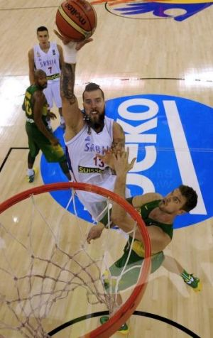 Serbia's centre Miroslav Raduljica (left) jumps over Brazil centre Tiago Splitter.