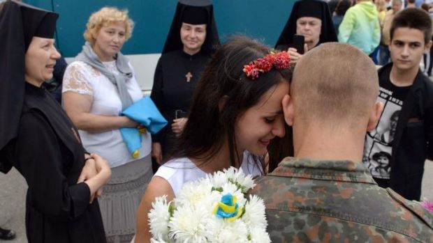 A Ukrainian soldier embraces his girlfriend during a welcome ceremony in the western city of Lviv as 146 soldiers return ...