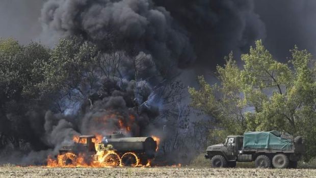 The fighting goes on: Vehicles burn on a country road in eastern Ukraine.