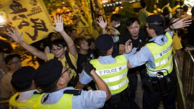 Pro-democracy activists clash with police outside the hotel where top Communist Party official Li Fei was staying in ...