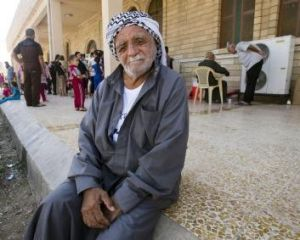 A man sits in the shade at a UN internally displaced persons camp in Erbil, Iraq.
