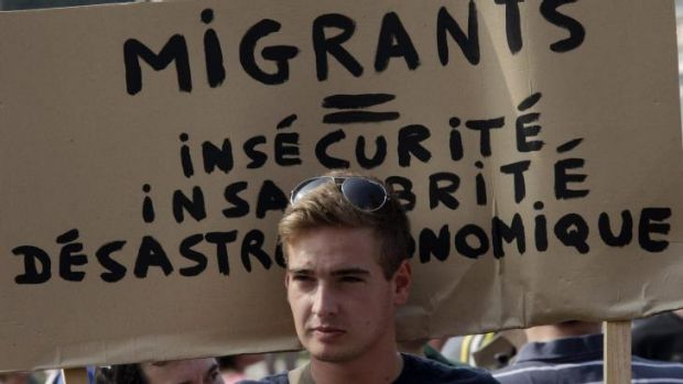"Far-right: A man holds a banner at a protest in Calais on Sunday that reads ""Migrants equal insecurity, unhealthiness ..."