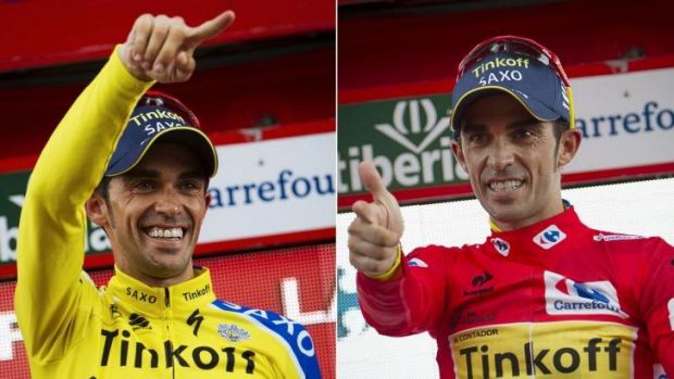 Tinkoff's Spanish cyclist Alberto Contador celebrating on the podium after retaining the red jersey (R) and winning the ...