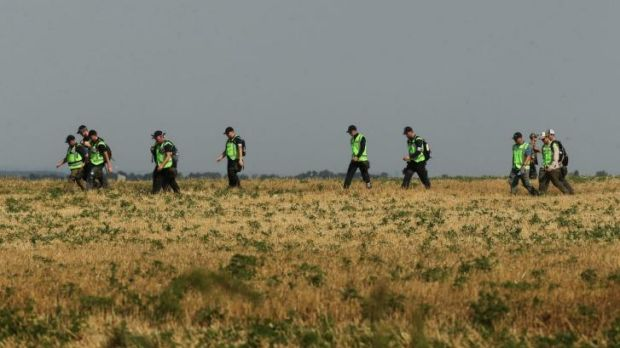 Australian and Dutch police walk across a field during their search last month for remains of victims of MH17.
