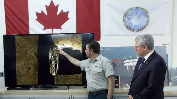 Canada's Prime Minister Stephen Harper (right) listens as Parks Canada's Ryan Harris talks about an image showing one of ...