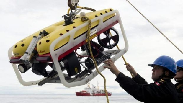 A crew member of the HMCS Kingston loads an remote underwater vehicle part of the Victoria Strait Expedition, west of ...