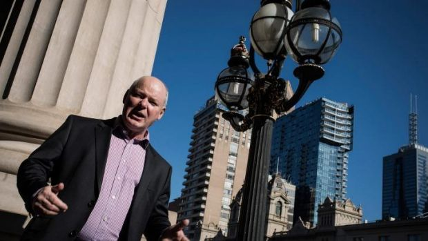 Quick fix?: Gerard Vaughan on the Parliament steps with the city's changing city skyline rising in the background.