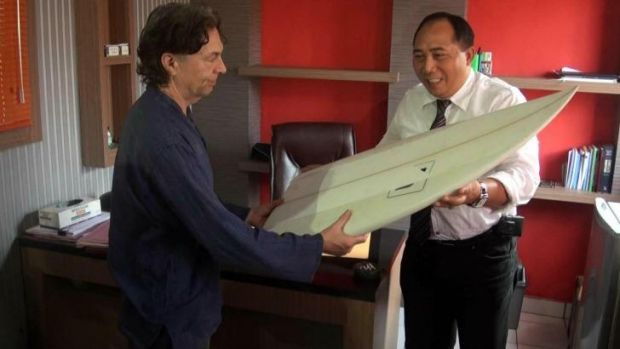 Brother John Maynard collects his missing brother's surfboard from Indonesian police.