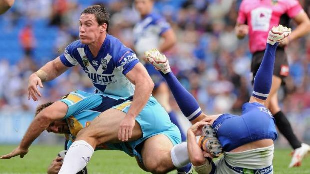 Josh Jackson and Josh Reynolds of the Bulldogs tackle David Taylor of the Titans.