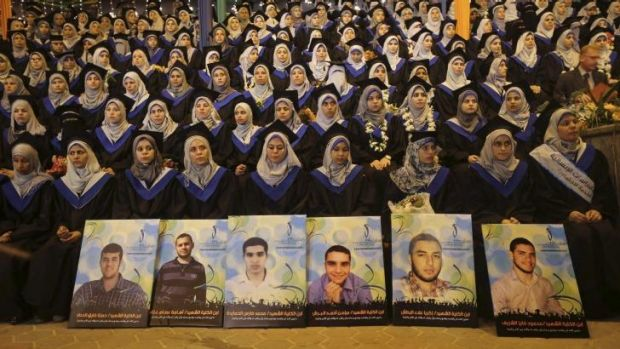 Palestinians graduating at Gaza City's University College of Applied Sciences on Wednesday sit behind pictures of ...