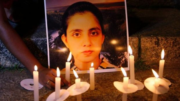 A student of a nursing college places a candle in front of a picture of nurse Jacintha Saldanha.