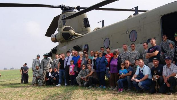Residents of the village of Gruta, in northern Poland, pose for a photo with US troops and their Chinook helicopter in ...