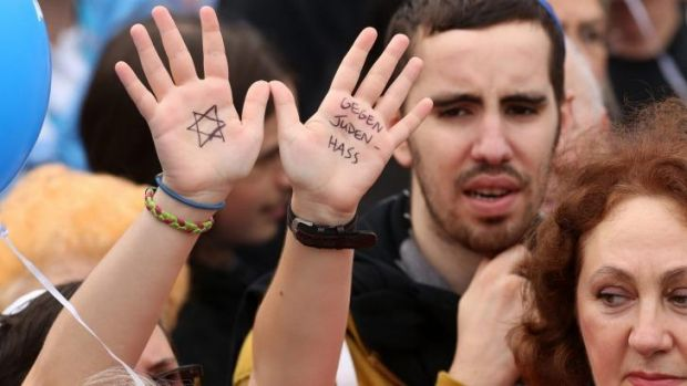 "Hands are held high with the Star of David and the words: ""Against hatred towards Jews."""