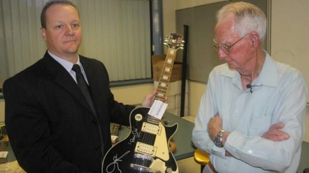 """Detective Senior Constable Lonie Horn holds up one of the recovered guitars as its owner, Leonard """"Merv"""" French, looks on."""